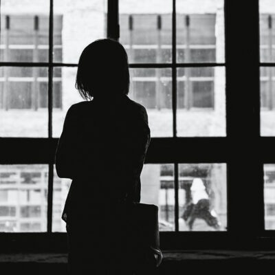 Lonely woman looking out window.