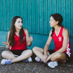 Two girls talking sitting on the ground in sports uniforms.