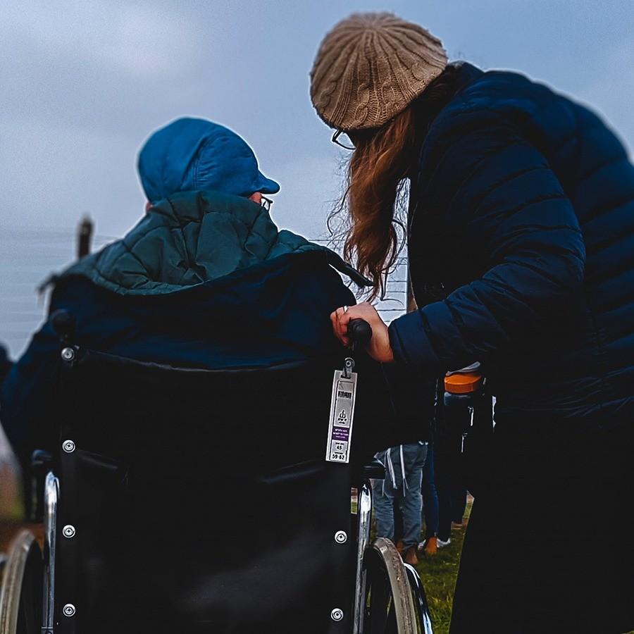 Foto de una mujer en silla de ruedas y su ayudante por Josh Appel en Unsplash