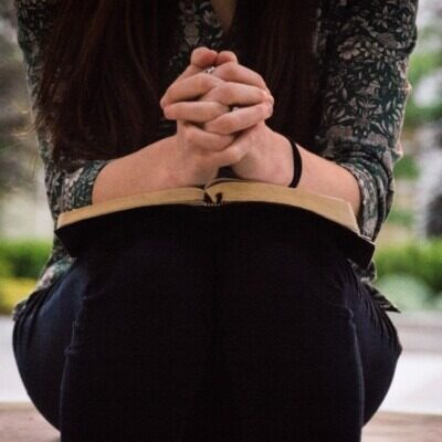 woman with folded hands on open Bible